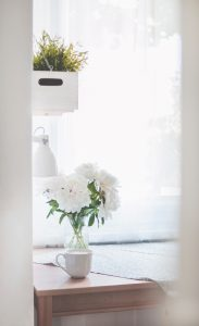 weißes Zimmer mit Blumen und Lampe